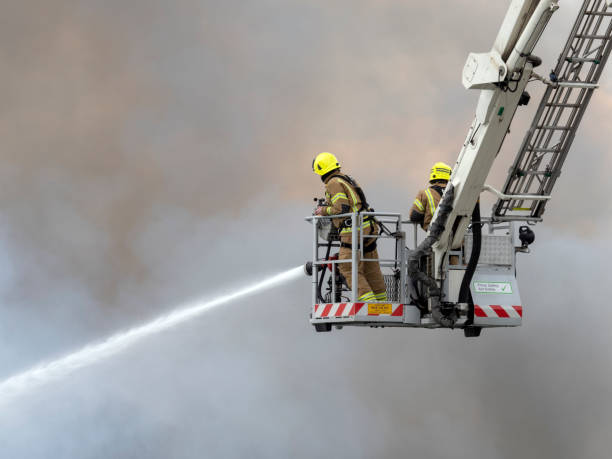 Firefighters using hoses on a fire stock photo
