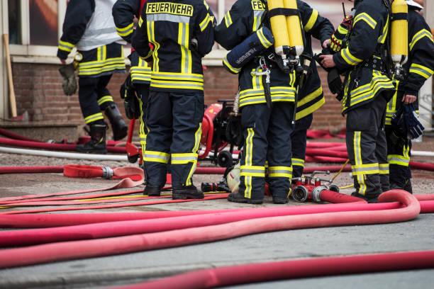 feuerwehr warten vor einem brennenden haus, deutschland, europa - feuerwehrmann deutsch stock-fotos und bilder