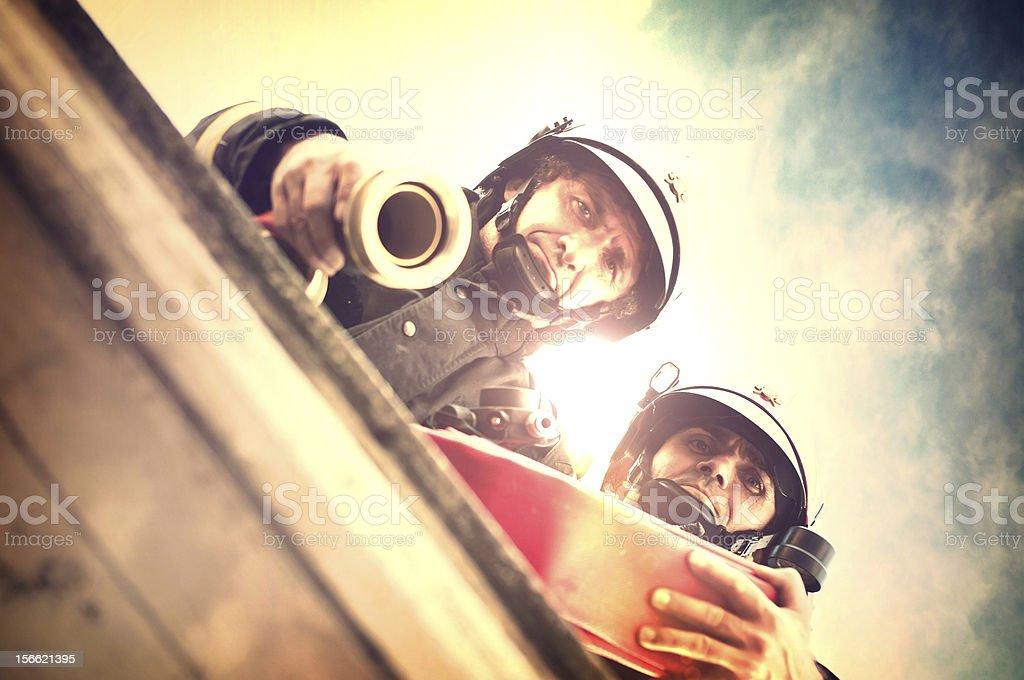 Bomberos con manguera para incendios en acción - foto de stock