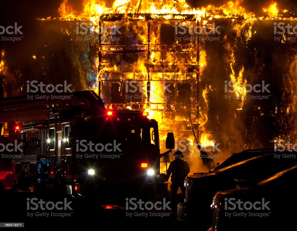 Firefighters with Fire Truck put out Building Fire stock photo
