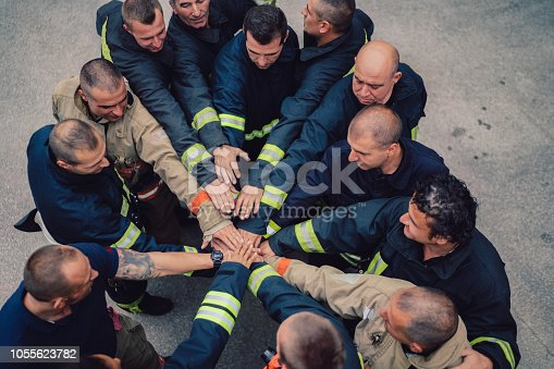 Directly above view of firefighters putting hands together