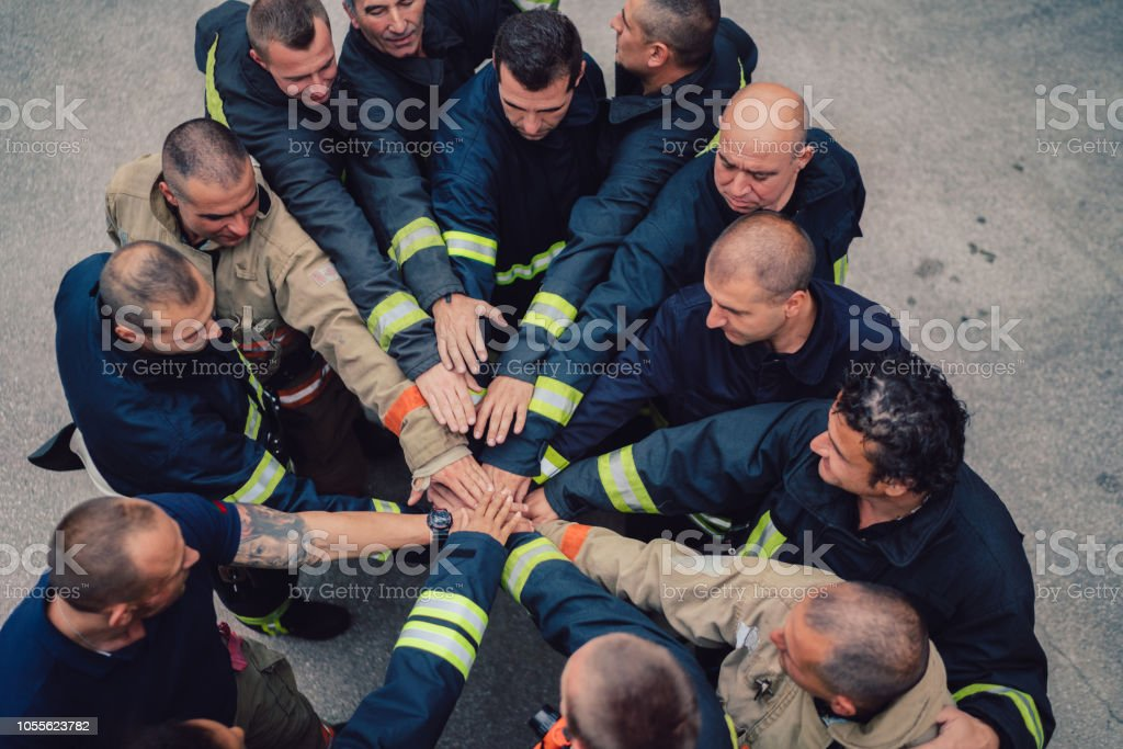Firefighters with hands stacked stock photo
