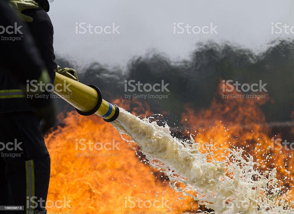 Firefighting foam. Fire-fighters applying foam to a fire. Color Image Stock Photo
