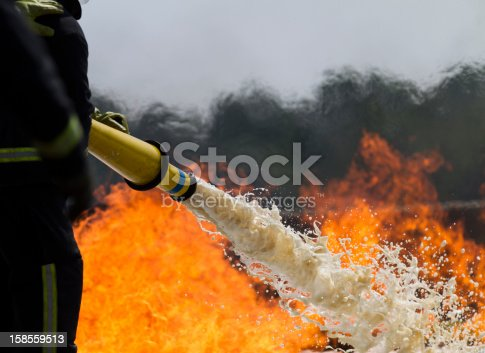 Fire-fighters applying foam to a fire.