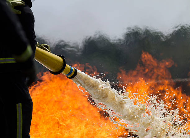 Firefighting foam. Fire-fighters applying foam to a fire. extinguishing stock pictures, royalty-free photos & images