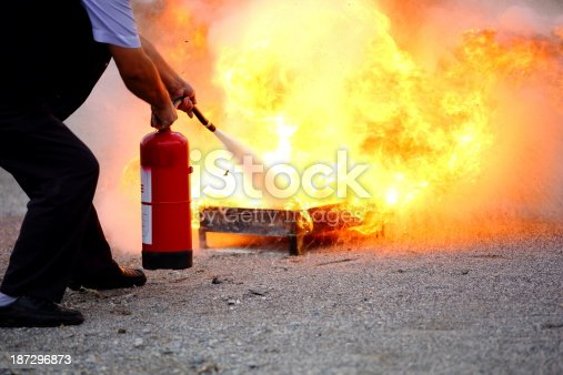Man puts out fire with extinguisher.