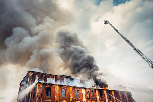 Firemen on the crane trying to extinguish a big fire. Grey clouds of smoke swirling out of an old abandoned building.