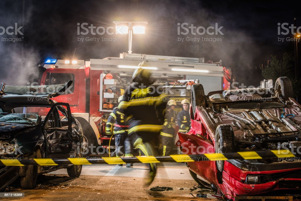 Firefigters at a car accident scene stock photo