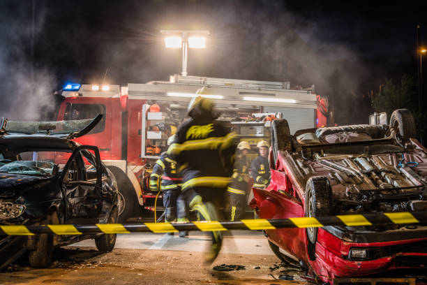 firefigters at a car accident scene - car accident stock photos and pictures