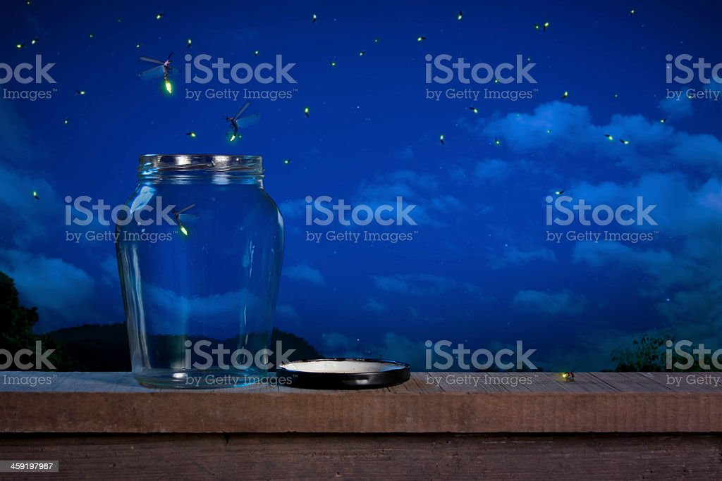Fireflies escape open jar on wooden beam into cloudy night stock photo