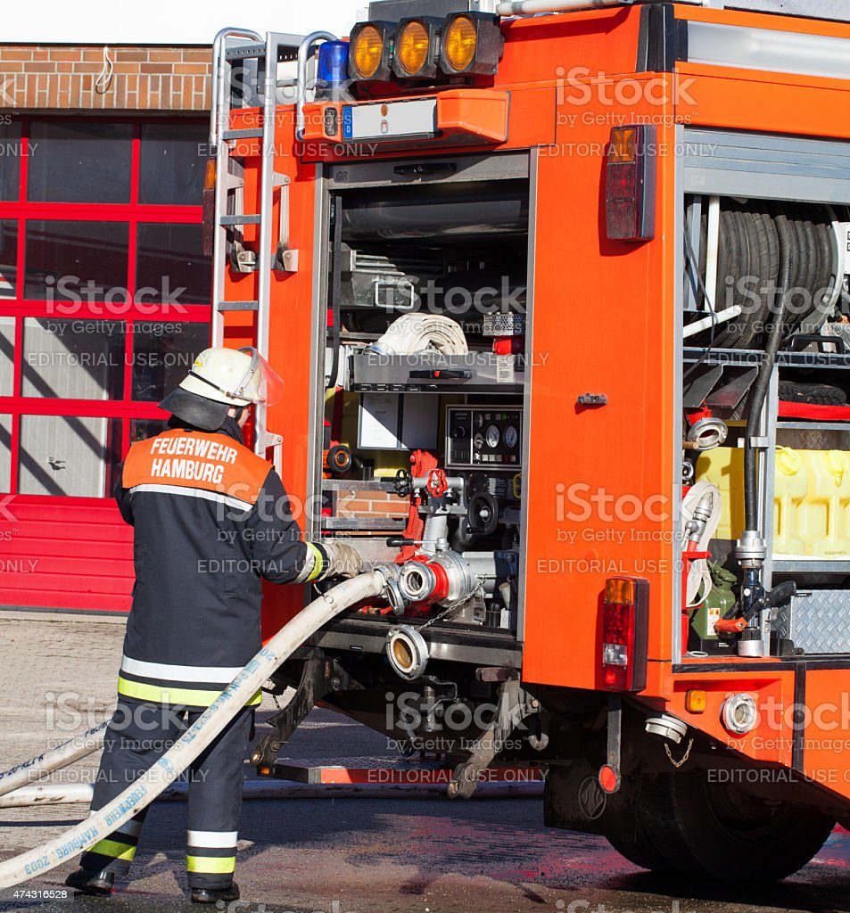 Fireman activates the water supply at the emergency vehicle stock photo