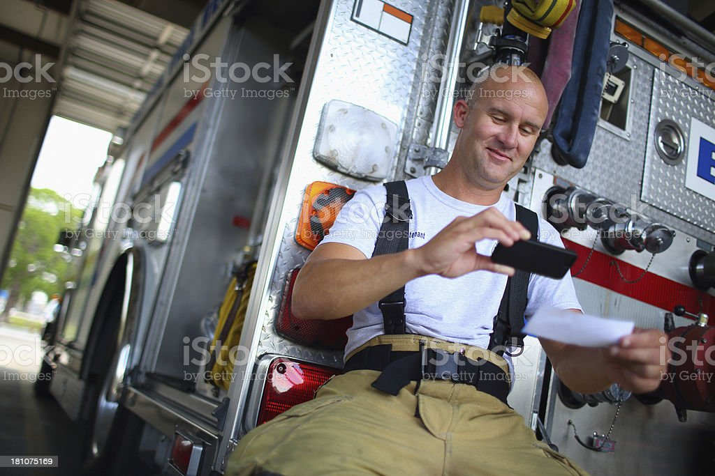 Fireman Depositing check with mobile phone stock photo