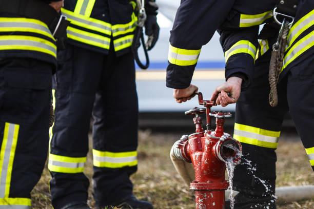 feuerwehrmann-bohrer, wasser verschütten verbrennungszone - feuerwehrmann deutsch stock-fotos und bilder