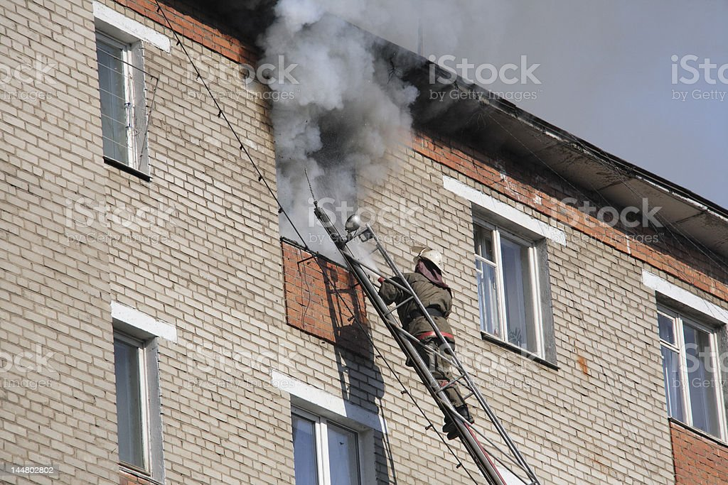 fireman extinguish a fire in high-rise apartment stock photo