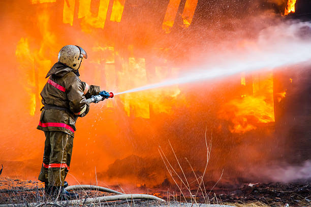 Fireman extinguishes a fire Fireman extinguishes a fire in an old wooden house extinguishing stock pictures, royalty-free photos & images