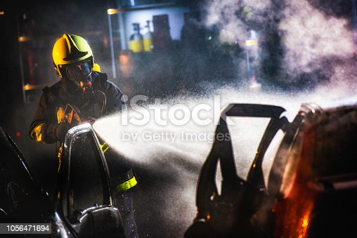 Firefighter with a fire hose spraying water onto a car in the middle of the night.