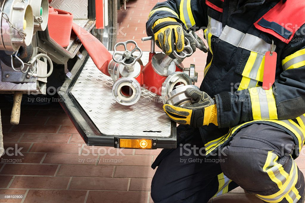Fireman in action connected a fire hose stock photo