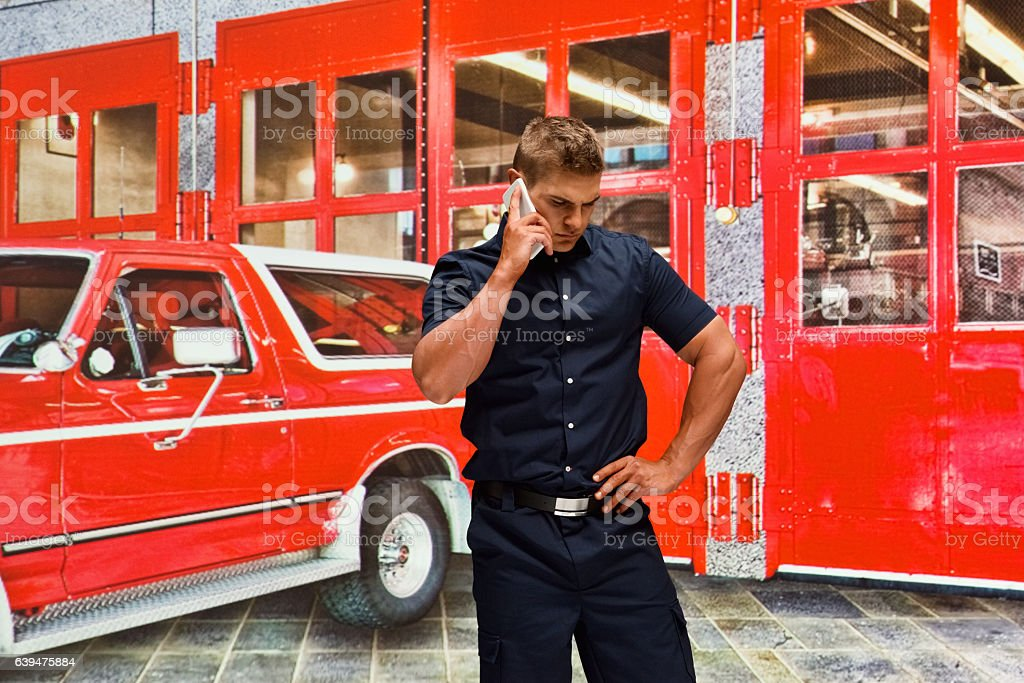 Fireman on phone in front of fire station stock photo