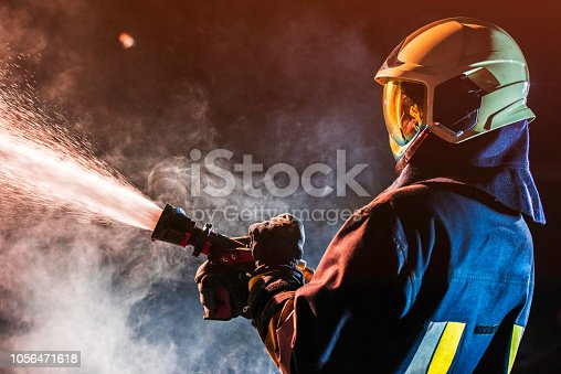 Side view of a firefighter in full gear operating a fire hose in a smokey area.