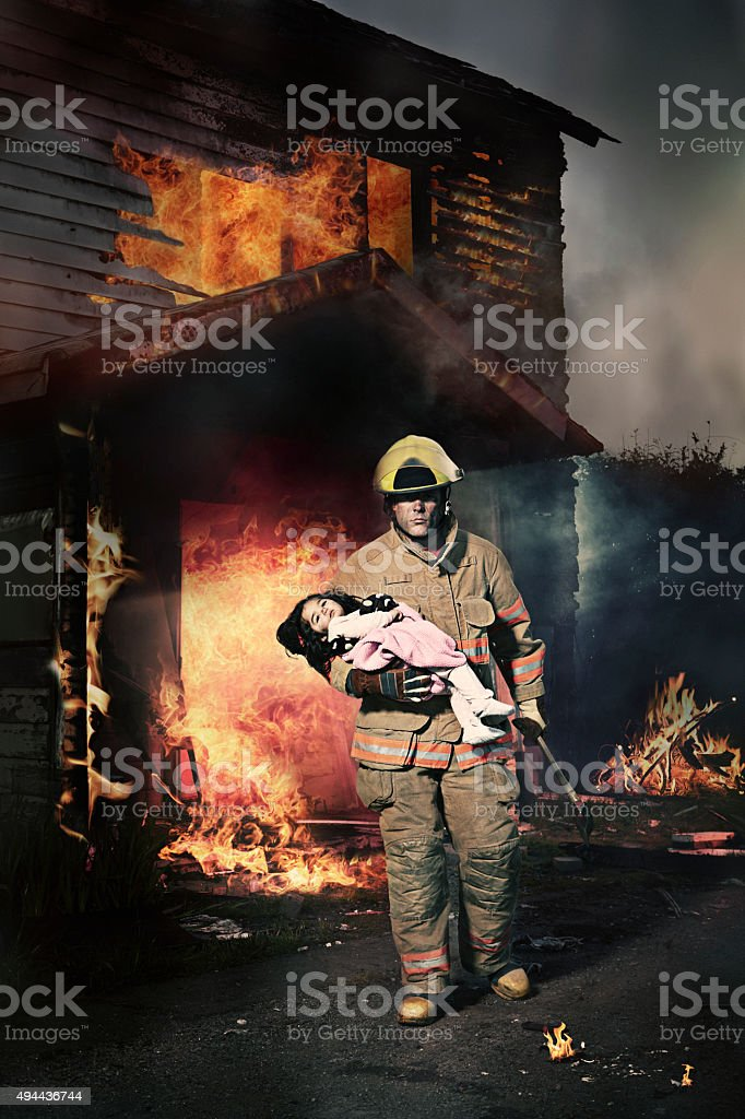 Fireman Rescuing a Baby From Burning House stock photo