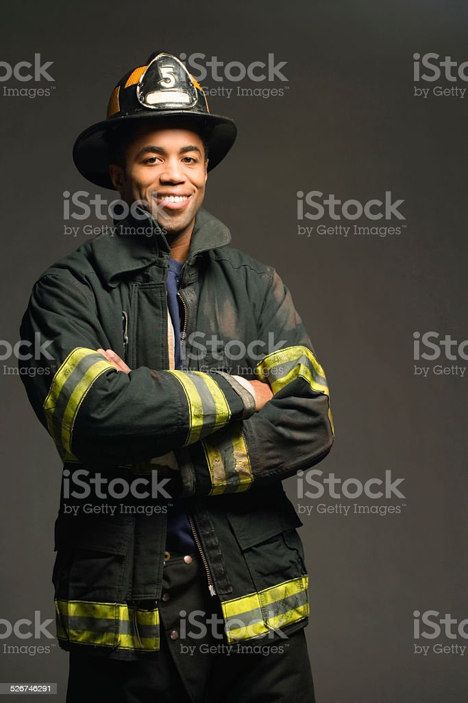Fireman smiling, on black background, portrait stock photo