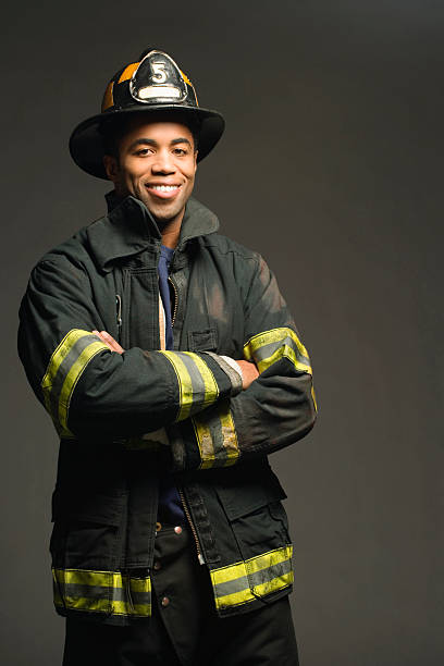 fireman smiling, on black background, portrait - firefighter stock photos and pictures
