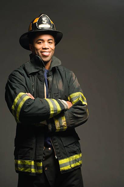 fireman sonriendo sobre fondo negro, vertical - bombero fotografías e imágenes de stock