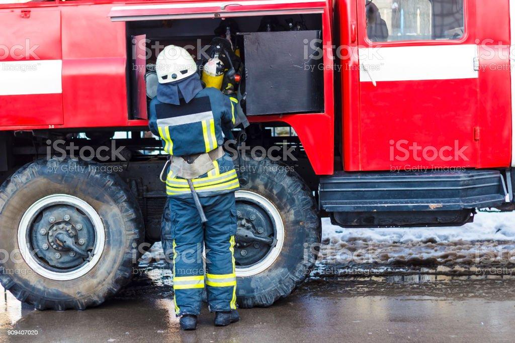 A fireman standing near a red fire engine and holding an oxygen...