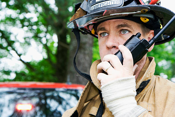 fireman talking on radio - firefighter stock photos and pictures