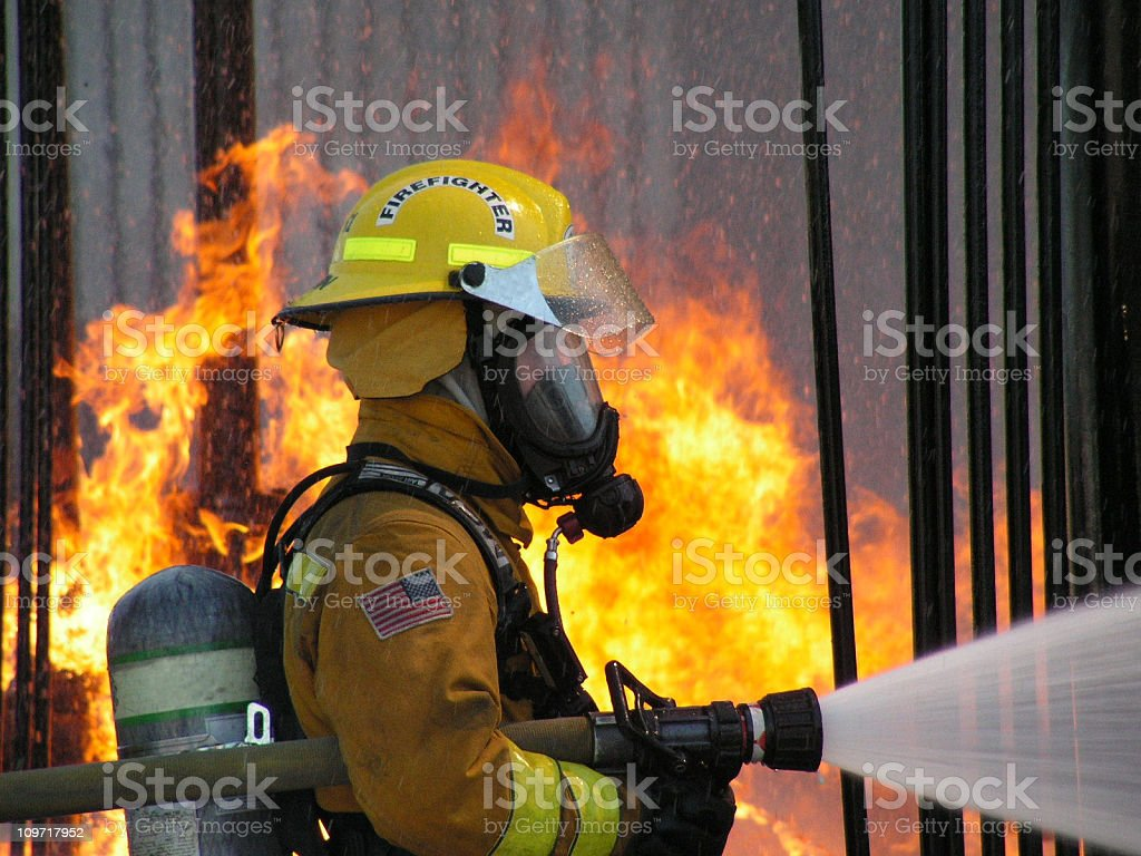 Fireman using hose with fire in background royalty-free stock photo