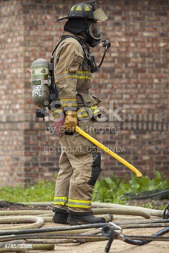 istock Fireman with an Axe Prepares to Enter a Burning Home 478573398