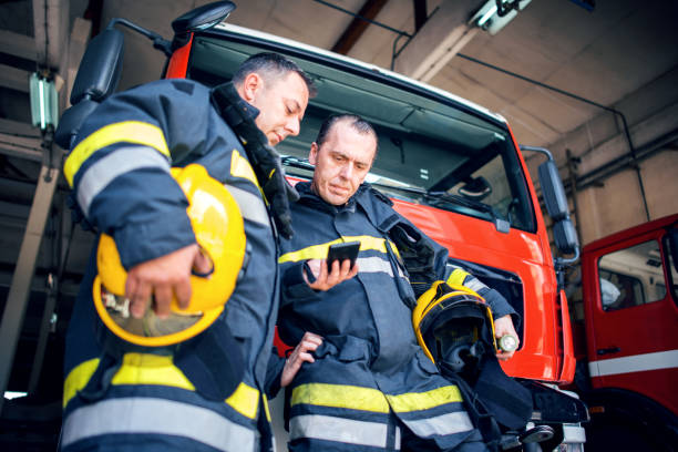 Fireman with radio set Firefighters using smart phone. smoke jumper stock pictures, royalty-free photos & images