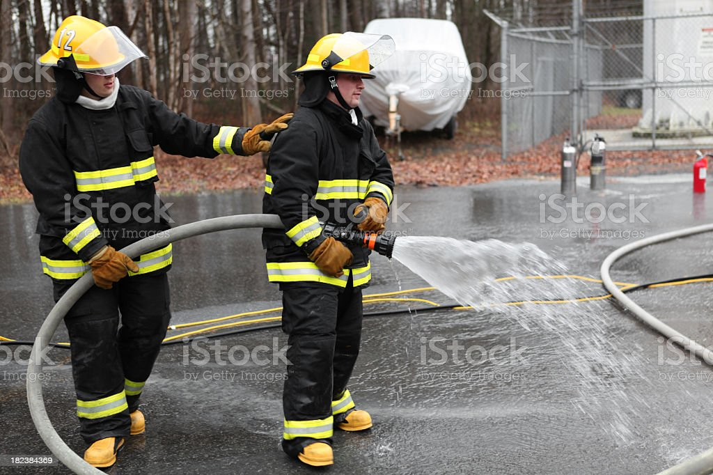 Firemen and fire hose royalty-free stock photo