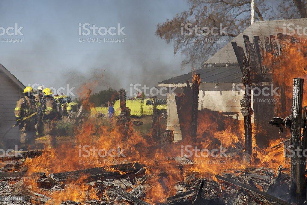 Firemen burning down an old barn stock photo