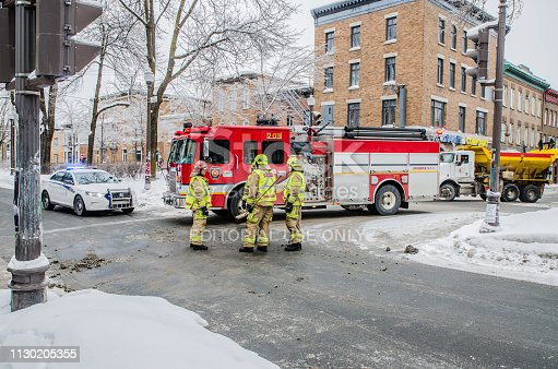 Firemen using broom to clean street corner from debris after car accident during winter day in Quebec city. Fire truck behind