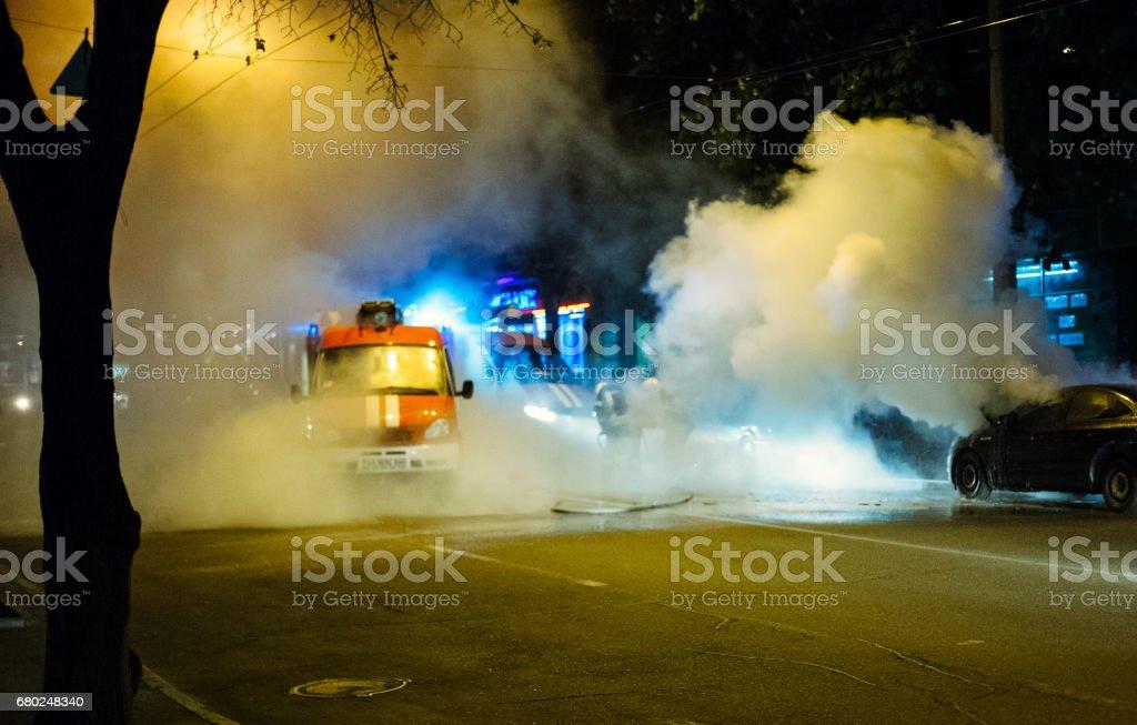 Firemen extinguishing a car fire stock photo