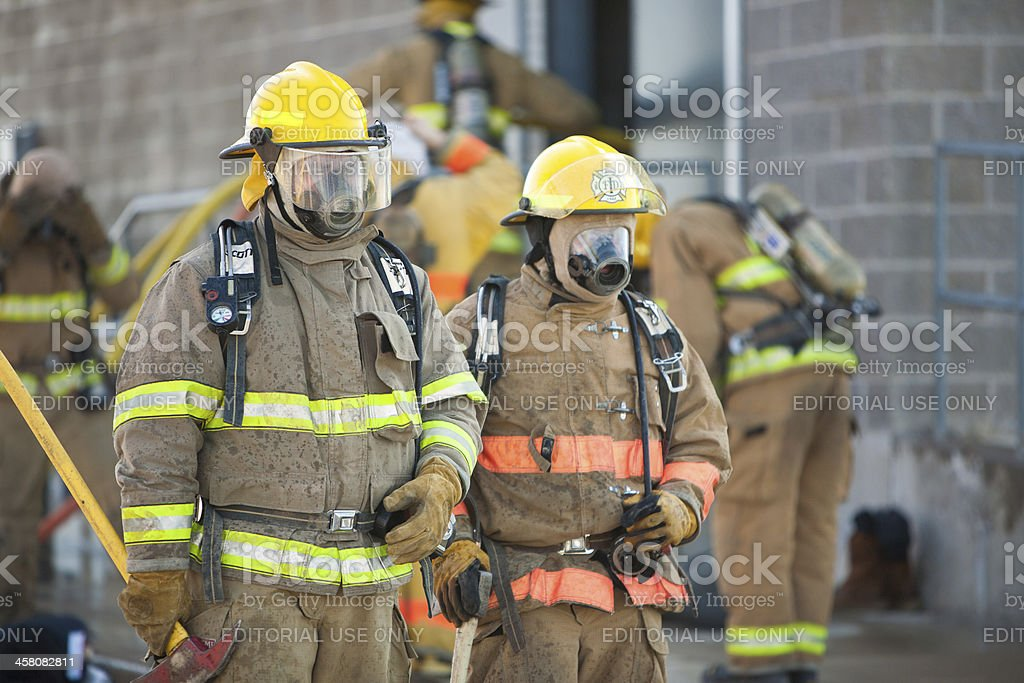 Firemen in Full Gear Outside of Building royalty-free stock photo
