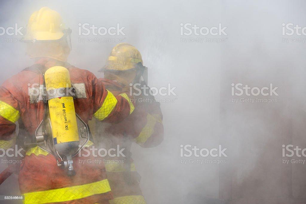 Zwei Feuerwehrleute in Betrieb umgeben mit Rauch – Foto