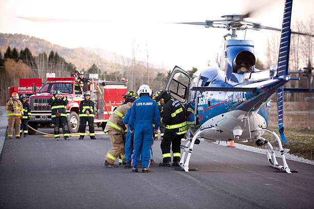 Firemen load a gurney into waiting helicopter stock photo