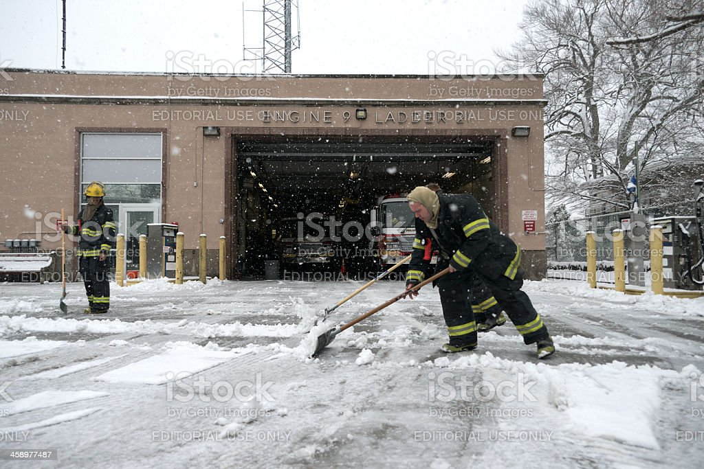 Firemen shovel snow at fire station royalty-free stock photo