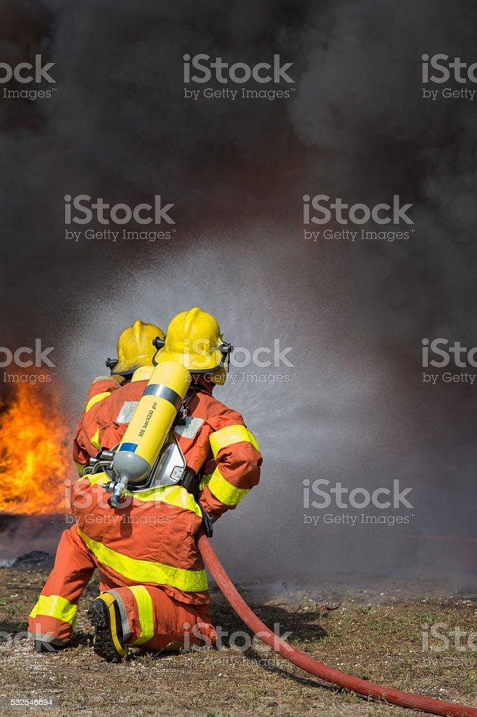 Zwei Feuerwehrleute sprühen Wasser im Brandschutz – Foto