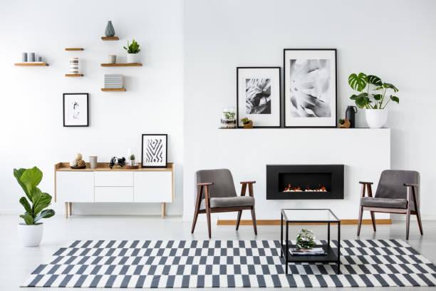 kamin zwischen grauen sessel im modernen wohnzimmer interieur mit plakaten. echtes foto - arten stock-fotos und bilder