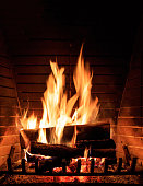 Burning fireplace. Cozy warm home, christmas time. Wood logs fire glowing in the dark. Vertical closeup view