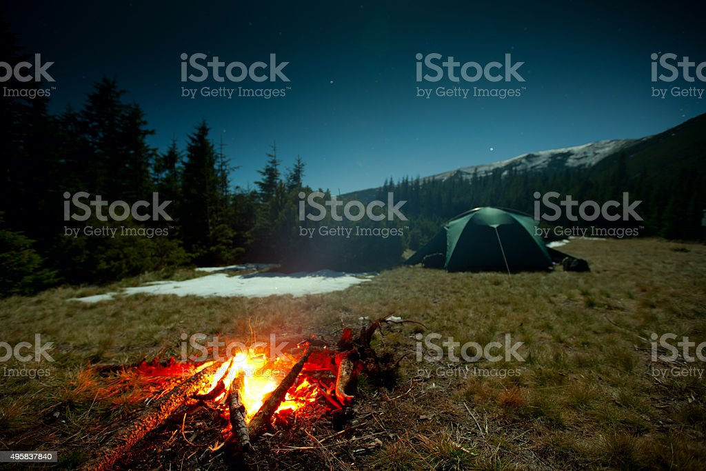 Fireplace during rest near tent at night stock photo