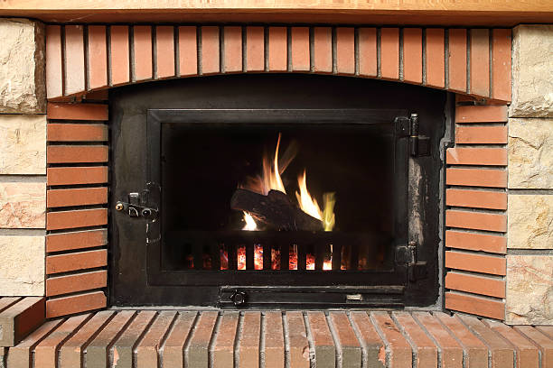 Fireplace in brick Fire in a  brick fireplace in winter. Front view. inserting stock pictures, royalty-free photos & images
