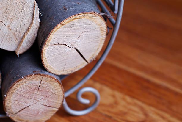 fireplace logs in holder on parquet stock photo