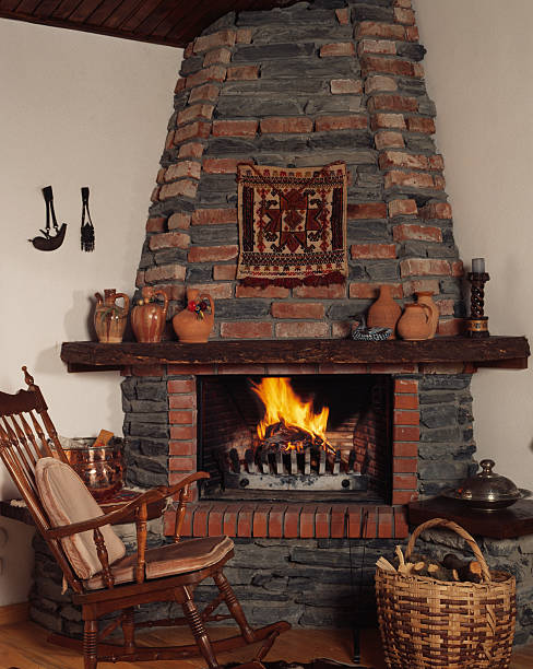 Fireplace Fireplace in a cosy living room with a rocking chair and a whisket grifare stock pictures, royalty-free photos & images