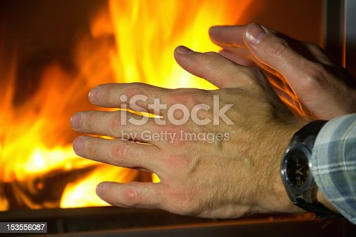men's hands by the fireplace