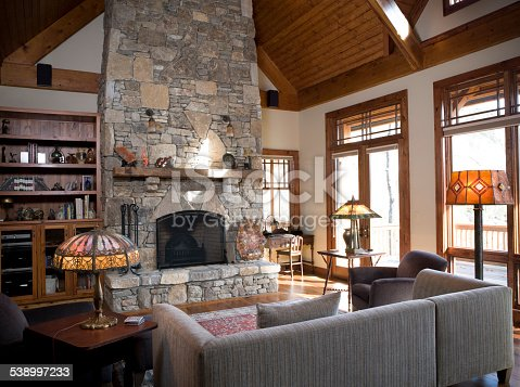 A den or living room with a beautiful stone fireplace and wooden beams.
