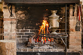 Large Fireplace with a burning fire and decorative items, comfort and atmosphere.